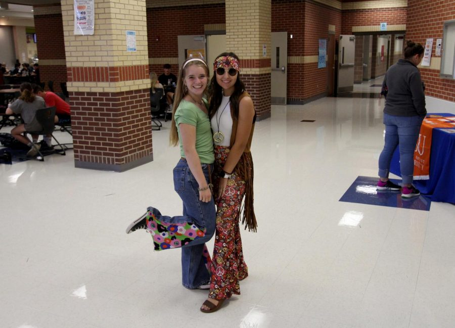 Freshmen Genevieve Jones and junior Brianna Siddall pose in their 70's outfits. Jones and Siddall are both on the cheer team and student council.