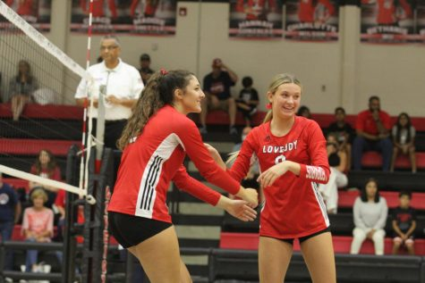 Junior middle hitter no.12 Hannah Gonzalez celebrates with senior setter no. 9 Averi Carlson. The volleyball team will be playing against The Colony on Friday in their first district game.