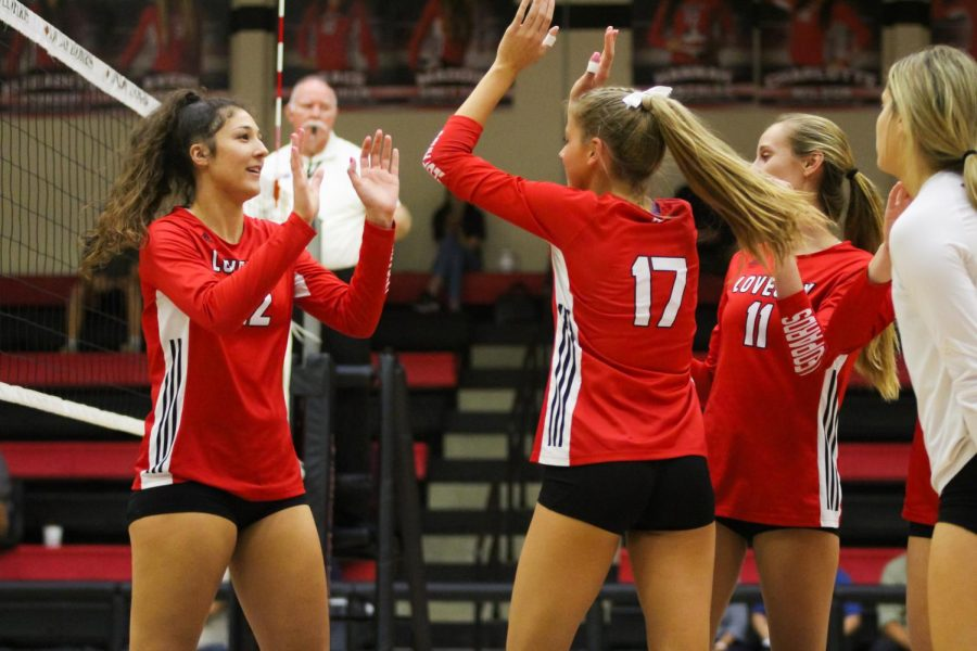 Sophomore hitter no. 12 Hannah Gonzalez high fives senior setter no. 17 Rosemary Archer. Gonzalez had just gotten a kill in the last play.