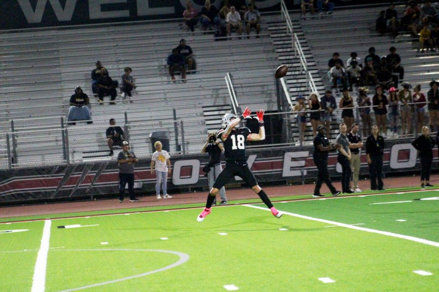 Sophomore wide receiver no. 18 Parker Livingstone catches the ball after a long throw to score a touchdown. The Leopards won 53-0.