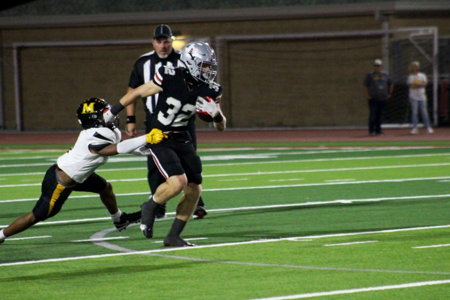 Sophomore running back no. 32 Mathew Mainord runs the ball after dodging a tackle from the opponent. Mainord rushed for a total of 107 yards.
