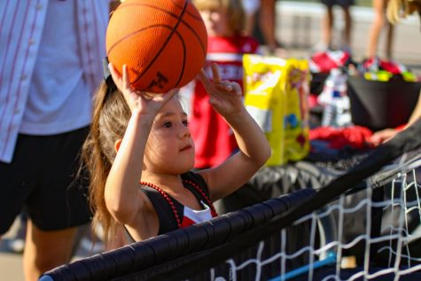 A young community member shoots the basketball to try and make it in the goal. The boys basketball team had the game set up for people to play.