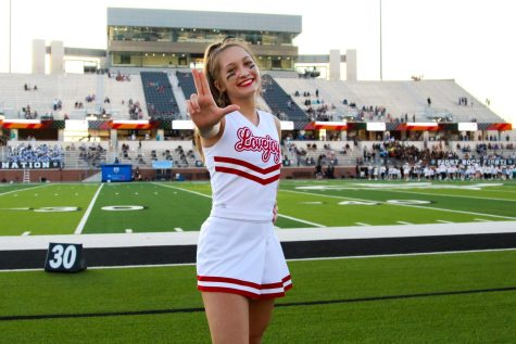 Junior Isabel Szymanski cheers on both the high school varsity team and on Lady Reign at Spirit of Texas. Szymanski has been cheering for seven years.