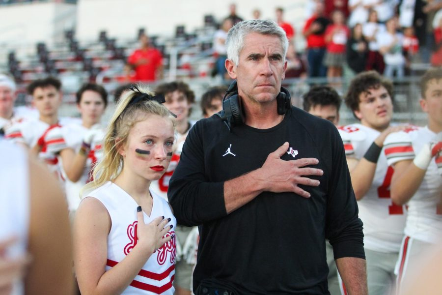 Junior cheerleader Morgan Johns stands with her dad, linebacker coach Jason Johns during the national anthem. The national anthem was sang by both the Lovejoy and Rock Hill choirs.