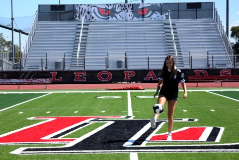 Junior Mary Mueth kicks a soccer ball up into the air. Mueth is on the Sting ENCL club team.